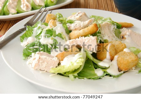 a bowl of Caesar salad with chicken and croutons