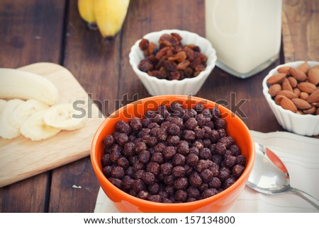 A bowl of cereal with almonds, bananas, milk and dried grapes - stock photo