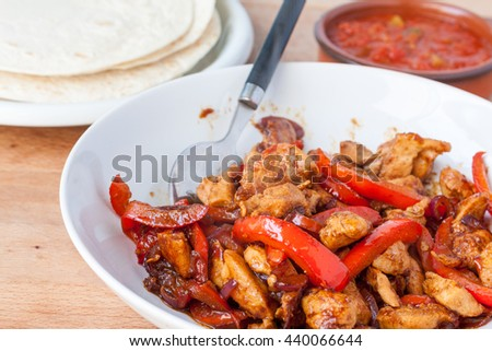 A bowl of chicken fajita mix with flour tortillas and salsa in the background