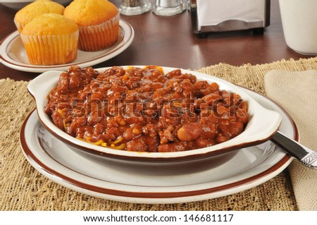 A bowl of chili con carne with cornbread muffins