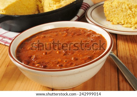 A bowl of chili with fresh baked cornbread - stock photo