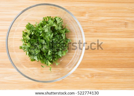 A bowl of chopped parsley over bamboo.