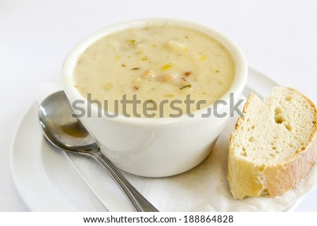 A bowl of clam chowder with bread and spoon. - stock photo