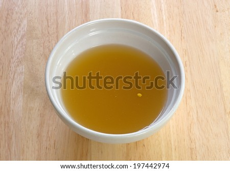 A bowl of clear chicken broth on a wood table top. - stock photo