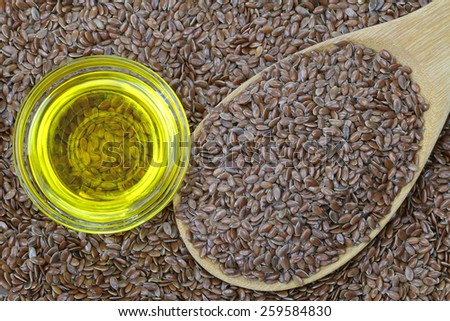 A bowl of cold pressed Linseed yellow oil on flaxseed background. flaxseed are seeds from flax plant. - stock photo