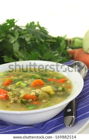 a bowl of colorful barley soup in front of white background
