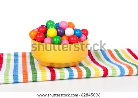 A bowl of colorful gumballs on a vibrant napkin. - stock photo