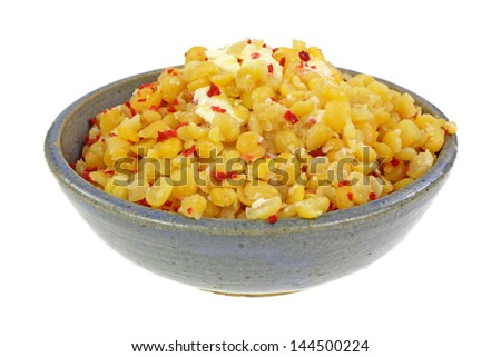A bowl of cooked yellow split peas with bacon bits and butter. - stock photo