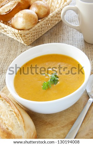 A bowl of coriander soup garnished with green coriander leaf accompanied with bread rolls - stock photo