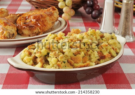 A bowl of corn bread stuffing with barbecued chicken in the background - stock photo