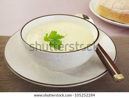 A bowl of creamy cauliflower soup with bread.