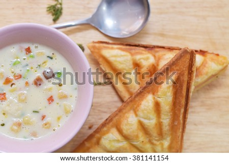 A bowl of creamy vegetable soup with Ham and Cheese Sandwich - stock photo