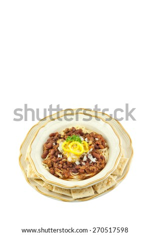 A bowl of delicious spicy chili spaghetti, topped with shredded cheese, onions and banana peppers, isolated on a vertical white background