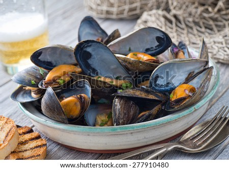 A bowl of delicious steamed mussels with grilled bread and beer on a rustic tabletop with fish net. - stock photo