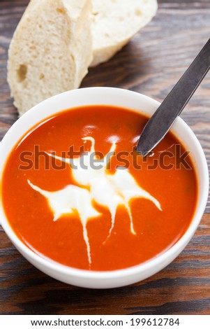 A bowl of delicious tomato soup with creme fraiche and sliced baguette on a wooden table - stock photo