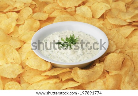A bowl of dip surrounded by potato chips. - stock photo
