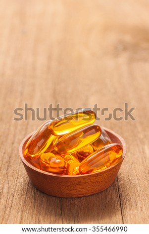 A bowl of Fish oil capsules on wooden texture, vertical view - stock photo