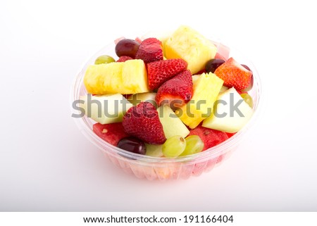 A bowl of fresh cut fruit on a white counter