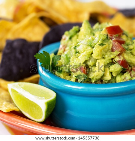 A bowl of fresh guacamole with corn tortilla chips and a wedge of lime. Intentional shallow depth of field. - stock photo