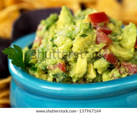 A bowl of fresh guacamole with corn tortilla chips. Intentional shallow depth of field. - stock photo
