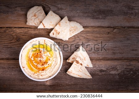 A bowl of fresh hummus, drizzled with olive oil and paprika, served with wedges of pita bread. - stock photo