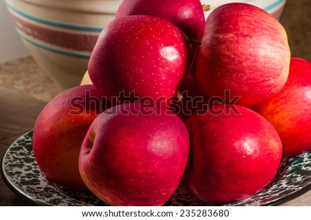 A bowl of fresh red apples and ceramic baking bowl - stock photo