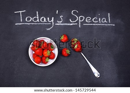 A bowl of fresh ripe strawberries with spoon on a chalk board, as the special of the day. - stock photo