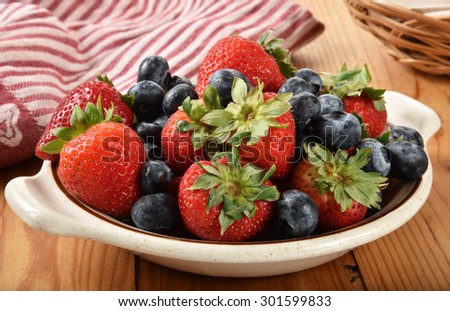 A bowl of fresh strawberries and blueberries on a rustic wooden table