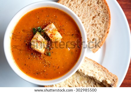 A bowl of fresh tomato soup in white ceramic bowl, garnished with herbs, croutons, seasoning and a drizzle of olive oil, and served with crusty wholemeal bread. - stock photo
