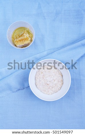 A bowl of freshly cooked oatmeal and honey on a light blue fabric background