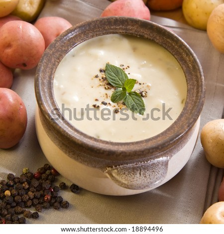 A bowl of freshly made creamy potato soup sprinkled with pepper and garnished with mint leaves - stock photo