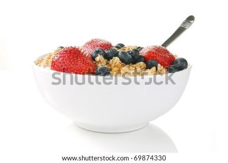A bowl of granola with strawberries and blueberries - stock photo