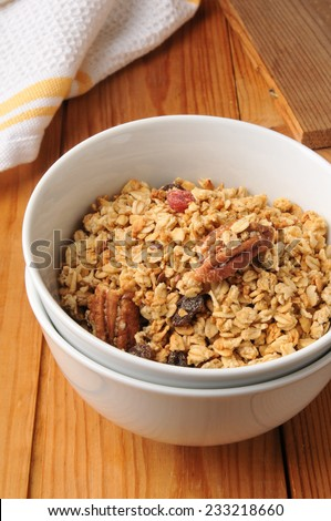 A bowl of healthy natural granola with pecans and raisins - stock photo