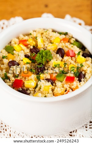 A bowl of healthy quinoa salad with black beans, tomato, corn, parsley and red and green bell peppers