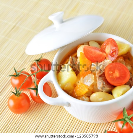A bowl of healthy vegetable soup with potato, carrot, tomatoes and meat. - stock photo