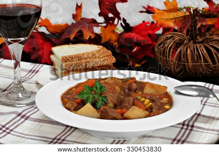 A bowl of homemade beef stew, and a glass of wine in a fall table setting. - stock photo