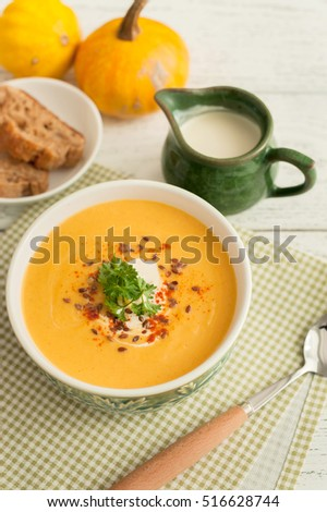A bowl of homemade creamy pumpkin soup on wooden background.