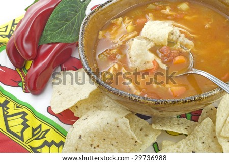 A bowl of hot homemade spicy Chicken Tortilla Soup, served with tortilla chips, horizontal with copy space - stock photo