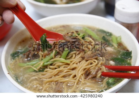 a bowl of hot steaming yee mee noodle served in spinach soup prepared with anchovies ikan bilis stock sprinkle with fresh organic shallots onions sold by hawker street food at malaysia china town - stock photo