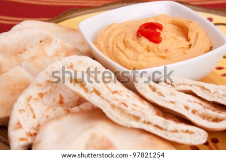 A bowl of hummus with pita bread surrounding it. Focus is on the hummus. - stock photo
