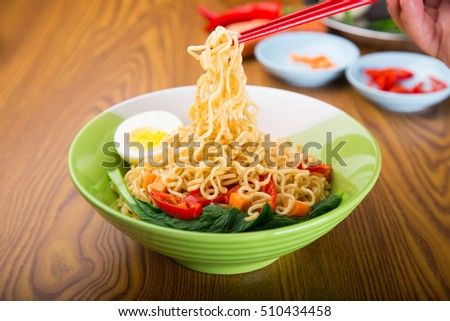 A Bowl of instant noodles on wooden table