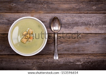 A bowl of leek and potato soup with bread croutons, over old wood table with fresh leeks and potatoes alongside - stock photo