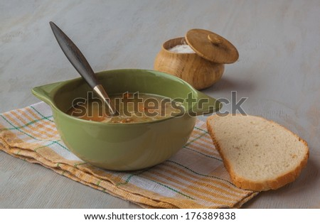 A bowl of lentil soup with a bread and salt on gray wooden table