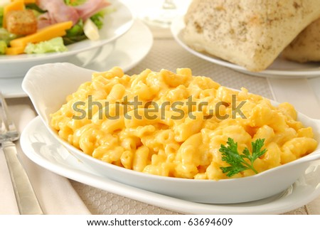 A bowl of macaroni and cheese on a table with rolls and a chefs salad - stock photo