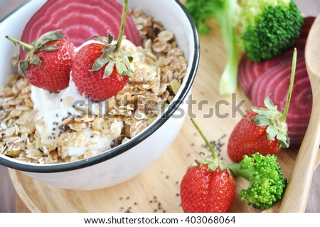 A bowl of muesli with fresh strawberries on wooden tray  - stock photo