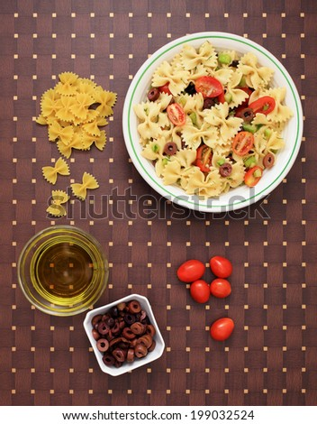 A bowl of pasta salad and the ingredients to make it. - stock photo