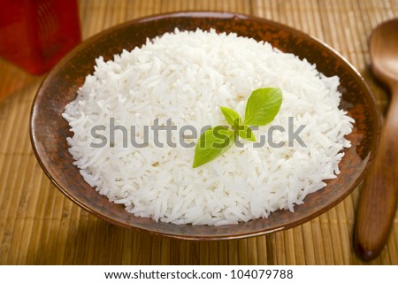 A bowl of perfectly cooked, plain Basmati rice, in an Asian style bowl, with a garnish of Thai Basil. - stock photo