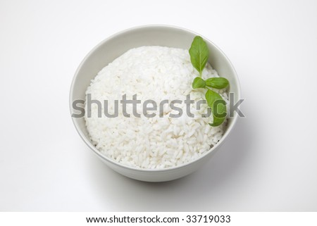 A bowl of perfectly cooked, plain Basmati rice, in an Asian style bowl, with a garnish of Thai Basil - stock photo