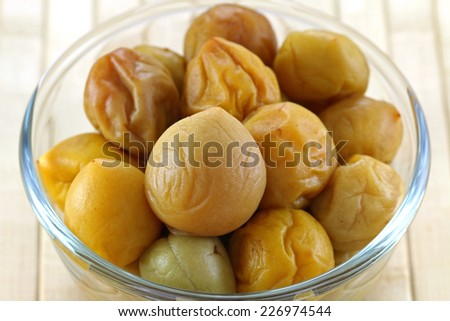 A bowl of pickled peach (Chinese plum, Japanese apricot), on a wooden mat - stock photo