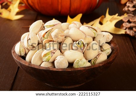 A bowl of pistachio nuts on a table with holiday decorations